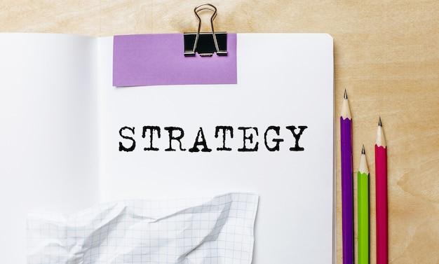 Strategie-text, geschrieben auf einem papier mit bleistiften auf dem schreibtisch im büro
