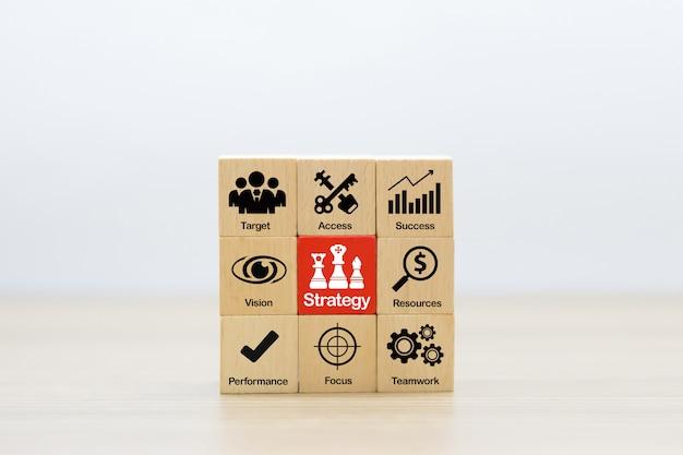 Strategieikonen auf holzklotz für erfolg, leistung, management und geschäftswachstum.