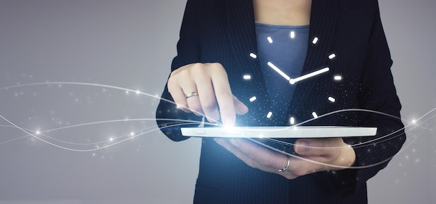Strategiekonzept für die effizienz von zeitmanagementprojekten. weiße tablette in der hand der geschäftsfrau mit digitalem hologramm-uhrzeichen auf grauem hintergrund.