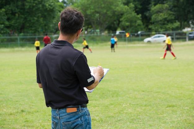 Strategischer männlicher trainer oder team-manager, der plan oder muster für fußball oder fußball zeichnet