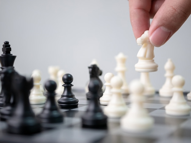Strategischer planungswettbewerb. hand, die den weißen pfand bewegt sich, schach spielend bewegend