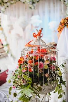 Strauß alstroemeria, rosen, farne in einer weißen käfigdekoration für hochzeitszeremonie