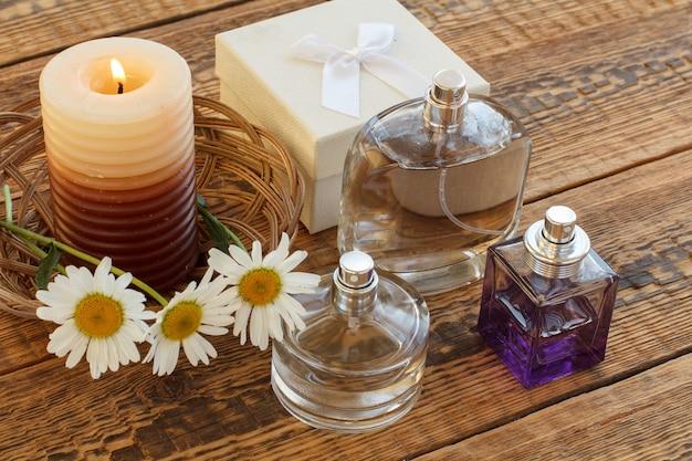 Strauß aus kamillen, parfums, einer brennenden kerze und einer weißen geschenkbox auf holzbrettern. ansicht von oben. urlaubskonzept.