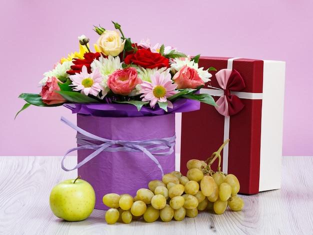 Strauß aus wildblumen, geschenkbox, trauben und einem apfel auf den holzbrettern