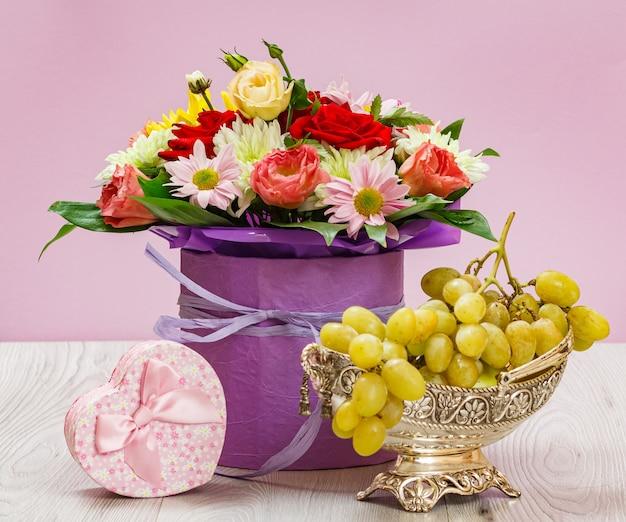 Strauß aus wildblumen, trauben und einer geschenkbox auf den holzbrettern