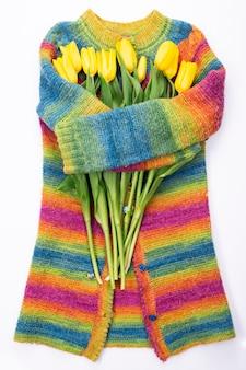 Strauß der gelben tulpen auf dem hintergrund eines mehrfarbigen gestrickten pullovers, draufsicht, strauß der gelben tulpen für frauentag, frühlingsblumenkonzept