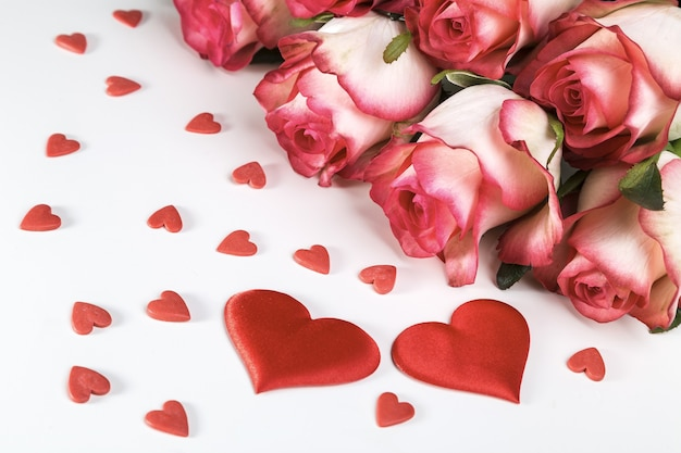 Strauß der hellen rosen und der roten herzen auf einem weißen hintergrund. valentinstag grußkarte.