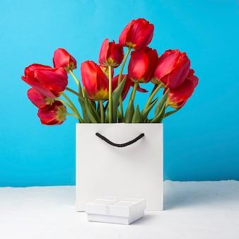 Strauß der leuchtend roten tulpen in einer weißen geschenktüte auf einem blau. konzeption von glückwünschen, überraschung und geschenk