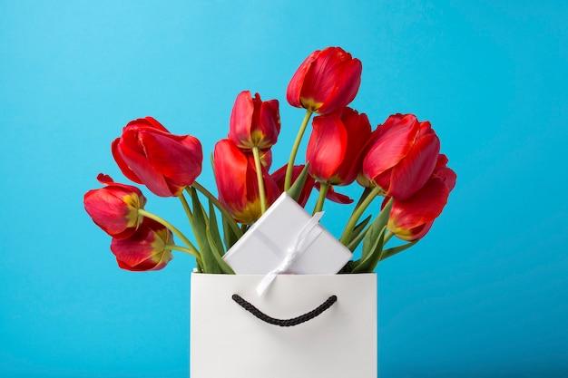 Strauß der leuchtend roten tulpen in einer weißen geschenktüte auf einem blauen hintergrund. konzeption von glückwünschen, überraschung und geschenk