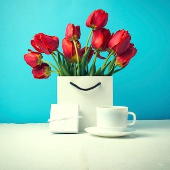 Strauß der leuchtend roten tulpen in einer weißen geschenktüte, weiße tasse mit kaffee, weiße geschenkbox auf einem blauen. konzept glückwünsche, überraschungen und geschenke