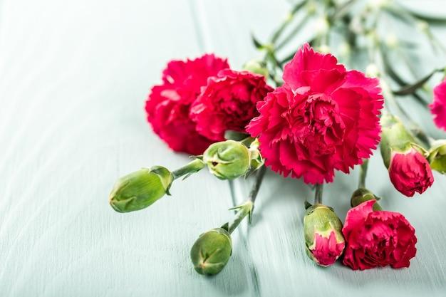 Strauß der rosa nelke auf heller türkisfarbener holzoberfläche. grußkarte mit kopierraum