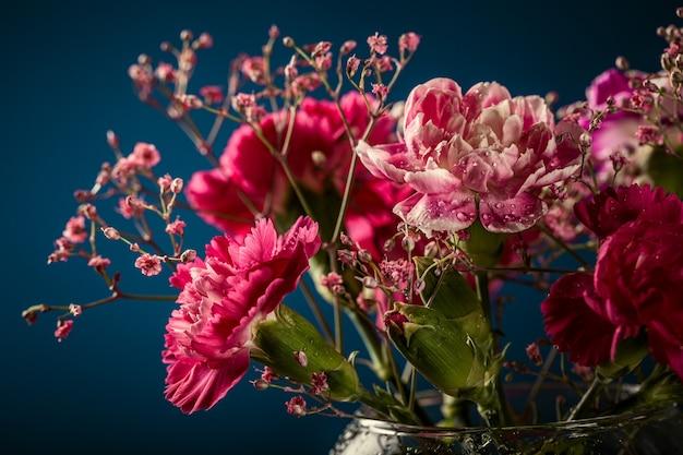 Strauß der rosa nelke in der glasvase auf dunkelblauer oberfläche. muttertag, geburtstagsgrußkarte. speicherplatz kopieren