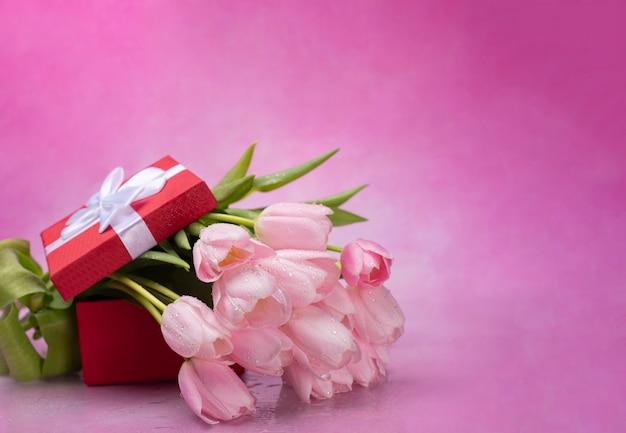 Strauß der rosa tulpen und einer roten schachtel mit einem geschenk auf einem rosa hintergrund