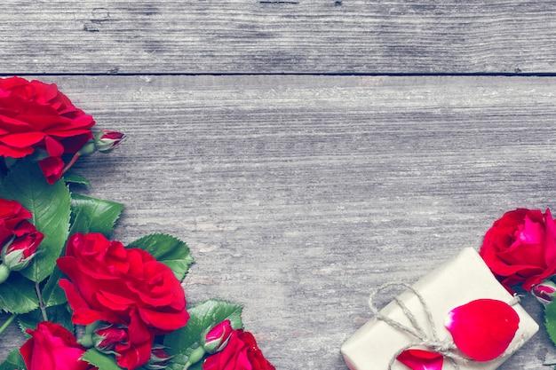 Strauß der roten rosen und der geschenkbox auf rustikalem hölzernem hintergrund