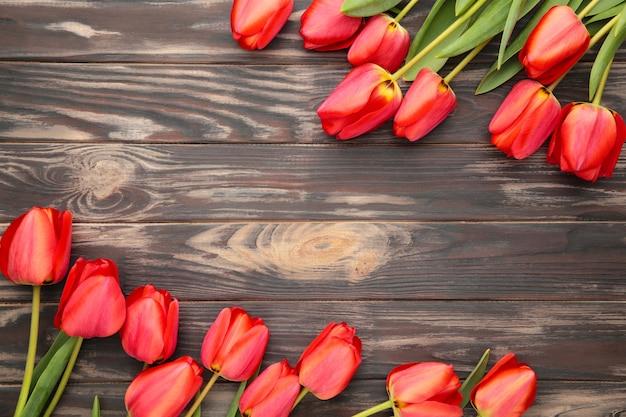 Strauß der roten tulpen auf braunem hölzernem hintergrund. muttertag und valentinstag hintergrund.
