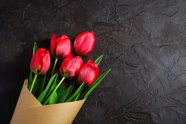 Strauß der roten tulpenblumen auf strukturiertem schwarzem hintergrund, kopierraum der draufsicht