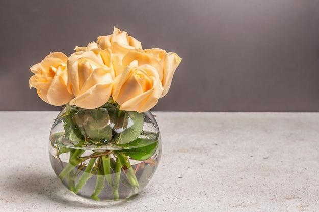 Strauß frischer beige rosen in einer vase. das festliche konzept für hochzeiten, geburtstage, 8. märz, mutter- oder valentinstag. grußkarte, dunkler hintergrund