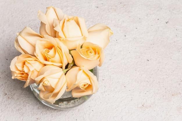 Strauß frischer beige rosen in einer vase. das festliche konzept für hochzeiten, geburtstage, 8. märz, mutter- oder valentinstag. grußkarte, heller hintergrund