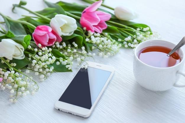 Strauß frischer frühlingsblumen und tee auf holz
