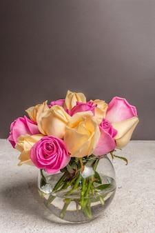 Strauß frischer mehrfarbiger rosen in einer vase. das festliche konzept für hochzeiten, geburtstage, 8. märz, mutter- oder valentinstag. grußkarte, dunkler hintergrund