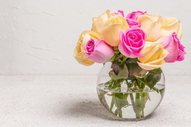 Strauß frischer mehrfarbiger rosen in einer vase. das festliche konzept für hochzeiten, geburtstage, 8. märz, mutter- oder valentinstag. grußkarte, heller hintergrund