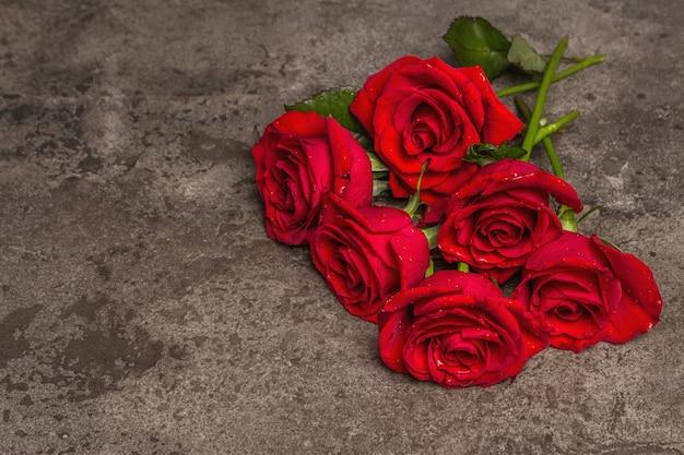 Strauß frischer roter rosen. das festliche konzept für hochzeiten, geburtstage, 8. märz, mutter- oder valentinstag. grußkarte, dunkler marmorhintergrund