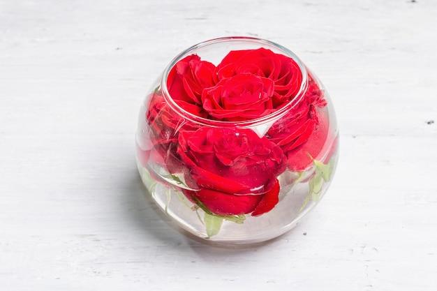Strauß frischer roter rosen in glasvase. das festliche konzept für hochzeiten, geburtstage, 8. märz, mutter- oder valentinstag. grußkarte, weiße holztafeln