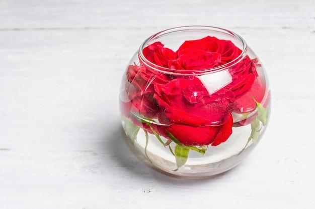 Strauß frischer roter rosen in glasvase. das festliche konzept für hochzeiten, geburtstage, 8. märz, mutter- oder valentinstag. grußkarte, weiße holztafeln Premium Fotos
