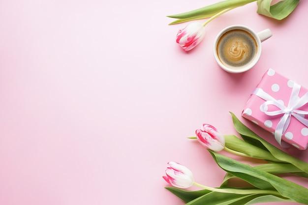 Strauß frischer tulpen mit kaffee und geschenkbox auf einem rosa hintergrund