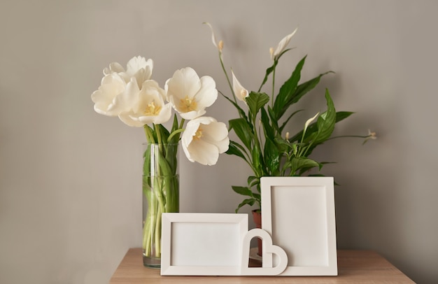 Strauß frischer weißer tulpen und leerer fotorahmen.