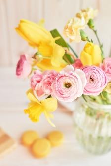 Strauß frühlingsblumen: tulpen, nelken, ranunkeln und narzissen in der vase auf dem tisch. muttertagsgruß