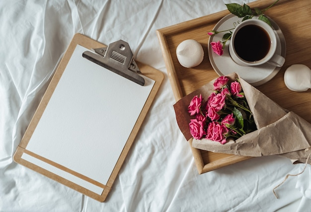 Strauß frühlingsblumen und eine tasse kaffee auf einem holztablett im bett