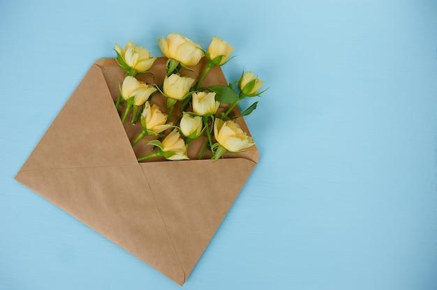 Strauß gelber rosen in einem umschlag auf blauer oberfläche
