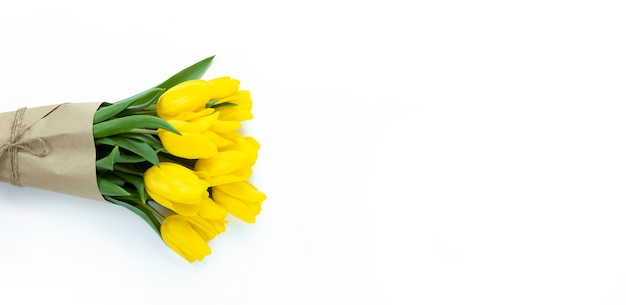 Strauß gelber tulpen, eingewickelt in bastelpapier auf einem weißen hintergrund mit kopienraum. Premium Fotos
