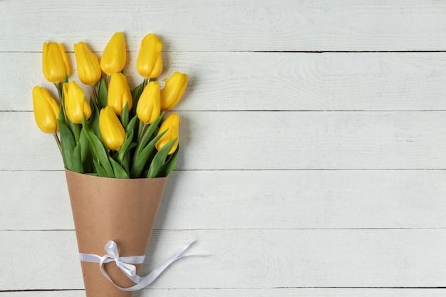 Strauß gelber tulpen, eingewickelt in bastelpapier auf weißem hölzernem hintergrund, flach lag mit kopienraum