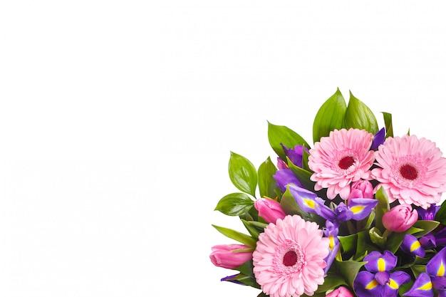 Strauß gerbera, iris und tulpen an einer weißen wand