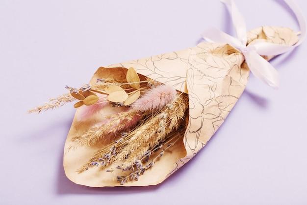 Strauß getrockneter blumen in kraftpapier auf lila hintergrund