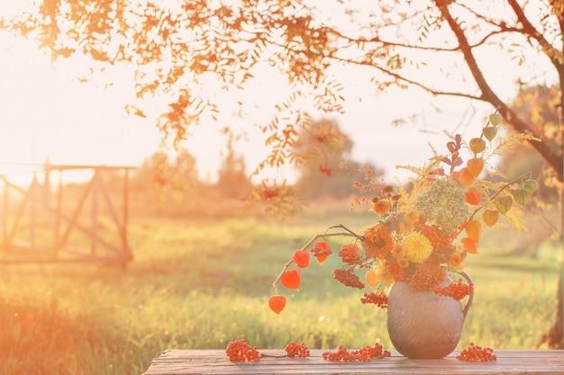 Strauß herbstblumen im rustikalen krug auf holztisch im freien bei sonnenuntergang