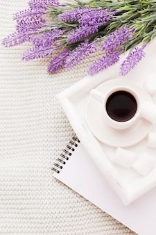 Strauß lavendel und tasse kaffee mit notizbuch