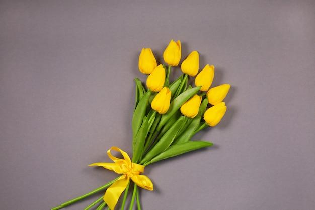 Strauß leuchtender gelber tulpen über der ultimativen grauen oberfläche. frühlingsblumen. farben des jahres 2021