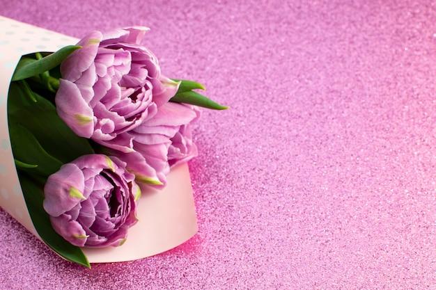 Strauß lila frühlingstulpen und platz für text für muttertag oder 8. märz auf einer rosa glitzeroberfläche draufsicht flacher stil