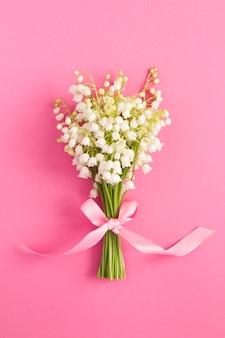 Strauß maiglöckchen mit rosa schleife auf der rosa oberfläche. lage vertikal. draufsicht. nahansicht. frühlingsblumenkonzept.