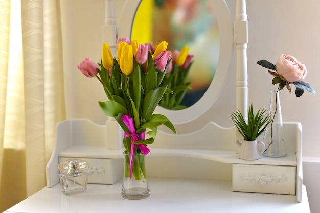 Strauß mehrfarbiger tulpen in einer vase auf dem weißen schminktisch in einem hellen raum