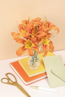 Strauß orange lilien mit goldenen scheren und bastelumschlag