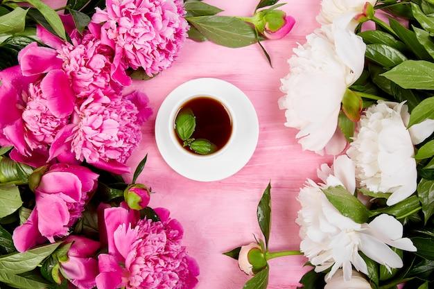 Strauß pfingstrosenblumen und tasse kaffee