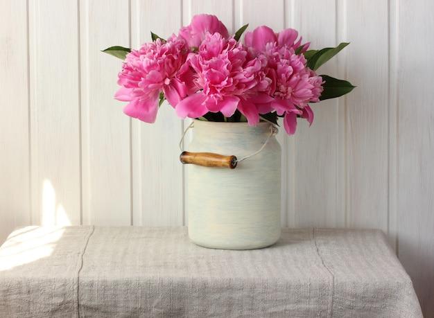 Strauß rosa pfingstrosen auf dem tisch.