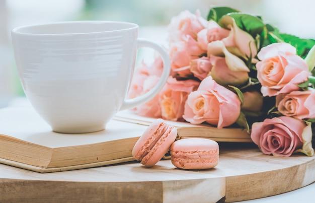 Strauß rosa rosen auf einem holzbrett mit einem glas oben auf dem buch und makronenplätzchen