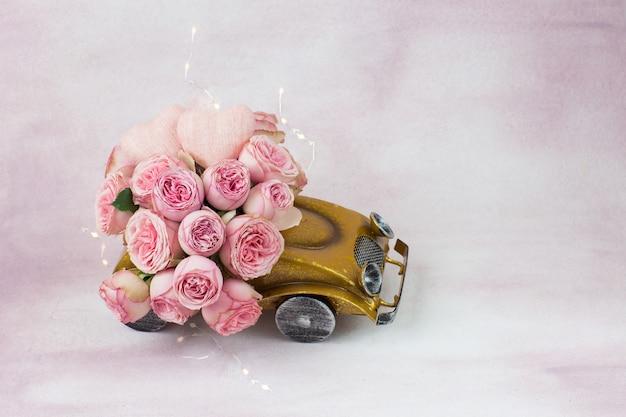 Strauß rosa rosen im auto, zwei herzen und eine girlande