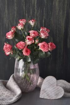 Strauß rosa rosen mit grauem wollschal und holzherz auf dunklem rustikalem holz Premium Fotos