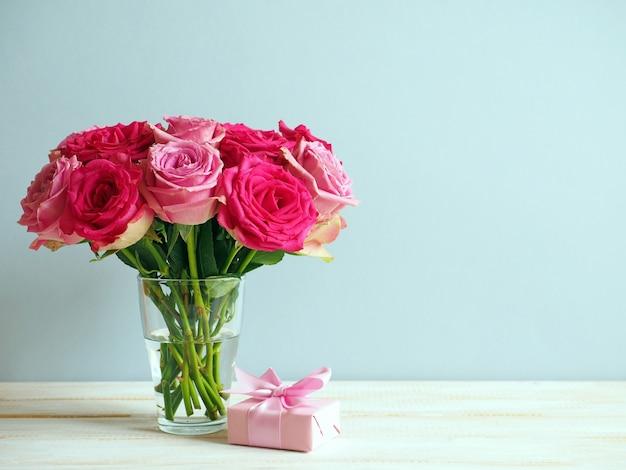Strauß rosa rosen und geschenkbox mit band